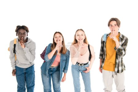 Smiling multiethnic teenagers with backpacks showing shh gesture isolated on white