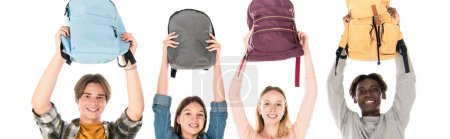 Panoramic shot of smiling multiethnic teenagers holding backpacks isolated on white