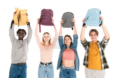 Cheerful multicultural teenagers holding backpacks and looking at camera isolated on white