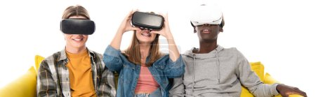 Panoramic shot of smiling multiethnic teenagers using vr headsets on couch isolated on white