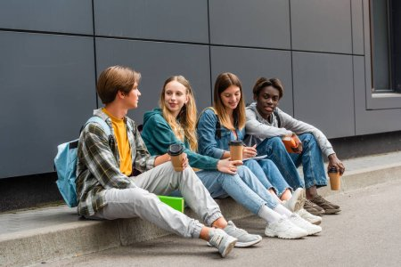 Photo for Positive multiethnic teenagers with coffee to go and books sitting on sidewalk near building - Royalty Free Image
