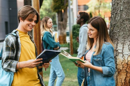 Photo for Selective focus of smiling teenagers with book and notebook standing near tree outdoor - Royalty Free Image