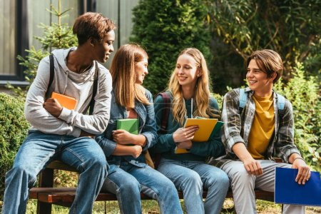 Smiling multicultural teenagers with books talking on bench outdoors