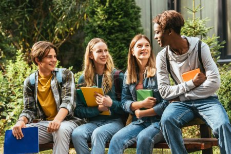 Smiling teenagers with books looking at african american friend on bench outdoors