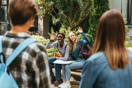 Photo pour Concentration sélective des adolescents multiethniques avec des cahiers agitant la main à des amis sur le banc - image libre de droit