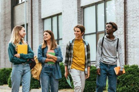 Photo pour Adolescents multiethniques regardant un ami avec un cahier tout en marchant dans la rue urbaine - image libre de droit