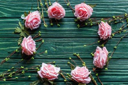 Photo pour Vue de dessus du fond vert en bois avec des branches florissantes, des roses - image libre de droit