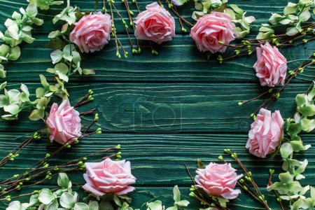 Photo for Top view of wooden green background with blossoming branches, roses - Royalty Free Image