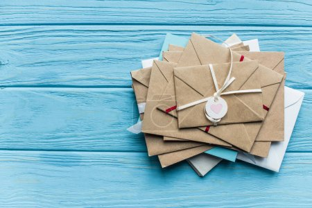 Photo for Top view of wooden blue background with envelopes and heart - Royalty Free Image