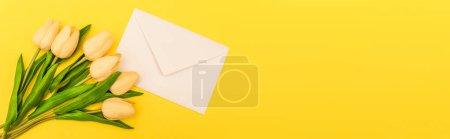 Photo pour Vue de dessus de l'enveloppe près des tulipes sur fond jaune, panoramique - image libre de droit