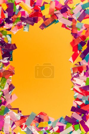 top view of colorful bright confetti frame on orange background
