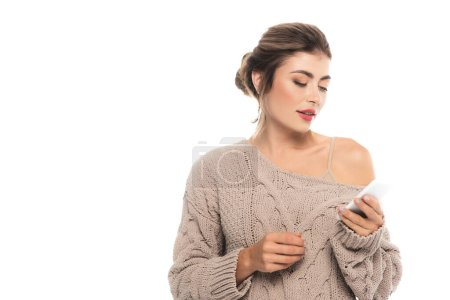 sensual, stylish woman in openwork sweater chatting on smartphone isolated on white
