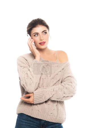 dreamy woman in trendy sweater talking on smartphone and looking away isolated on white