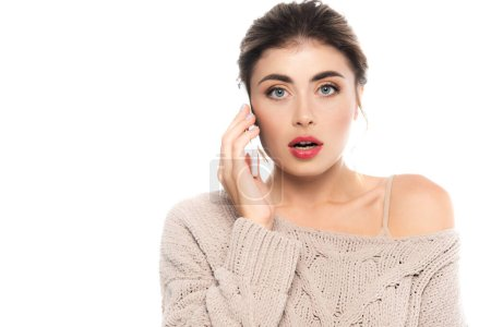 shocked woman in stylish openwork sweater looking at camera while talking on smartphone isolated on white