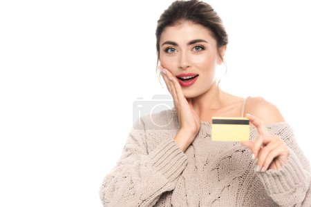 excited woman in trendy sweater showing credit card while looking at camera isolated on white
