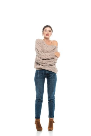 full length view of trendy woman in openwork sweater and jeans hugging herself while posing on white