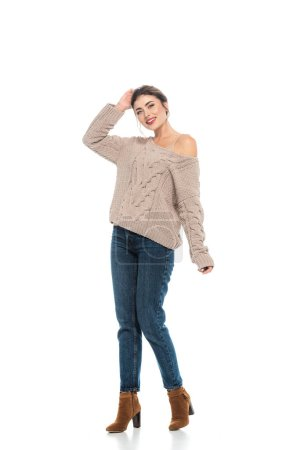Photo for Full length view of stylish woman in knitted sweater and jeans posing on white - Royalty Free Image