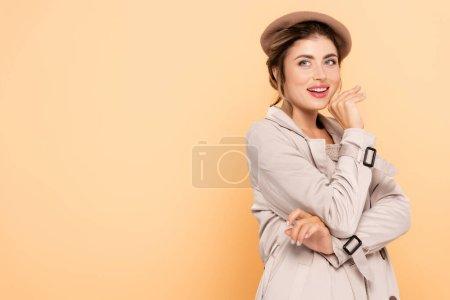 Photo pour Femme joyeuse en tenue d'automne élégant tenant la main près du visage tout en regardant loin sur la pêche - image libre de droit