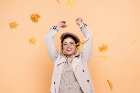 excited woman in trench coat and beret throwing yellow leaves on peach