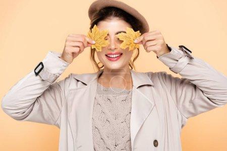 Photo pour Joyeuse femme en élégant trench coat et béret couvrant les yeux avec des feuilles jaunes isolées sur la pêche - image libre de droit