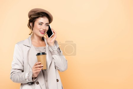 young woman in stylish autumn outfit holding coffee to go while talking on smartphone isolated on peach