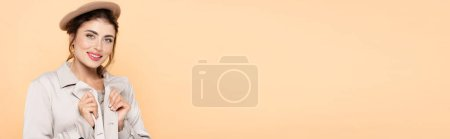 Photo for Website header of stylish woman in beret and trench coat looking at camera isolated on peach - Royalty Free Image