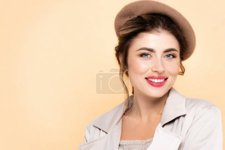 joyful woman in autumn outfit looking at camera while posing isolated on peach