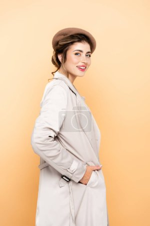 trendy woman in beret and trench coat looking at camera while posing with hand in pocket on peach