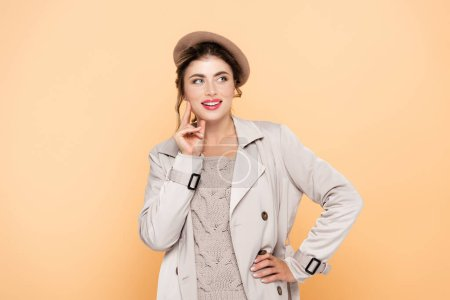 young woman in trendy autumn outfit looking away while posing with hand on hip on peach