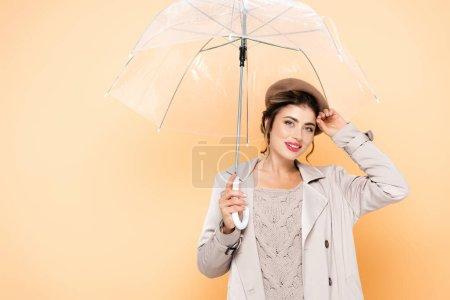 young stylish woman in autumn outfit looking at camera under transparent umbrella on peach