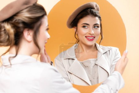 selective focus of joyful woman in beret and trench coat looking in mirror decorated with foliage on peach