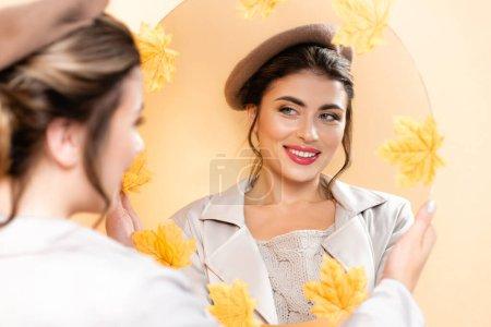 Photo pour Foyer sélectif de la jeune femme en trench-coat et béret regardant dans le miroir décoré de feuilles d'automne sur la pêche - image libre de droit