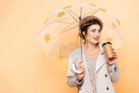 Photo pour Femme à la mode en béret et trench coat tenant café pour aller sous parapluie avec des feuilles d'automne sur la pêche - image libre de droit