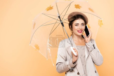joyful woman in fashionable autumn outfit talking on mobile phone under umbrella decorated with yellow leaves on peach