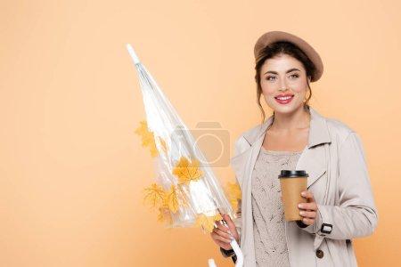 Trendfrau im Herbst-Outfit mit Coffee to go und Regenschirm mit gelben Blättern auf Pfirsich