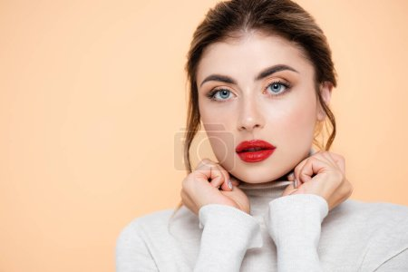 young woman in turtleneck holding hands near face while looking at camera isolated on peach