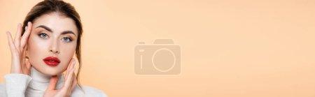 panoramisches Konzept der stilvollen Frau mit roten Lippen, die in die Kamera schaut, während sie Gesicht isoliert auf Pfirsich berührt
