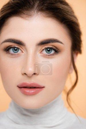 Nahaufnahme Porträt einer jungen Frau mit natürlichem Make-up, die isoliert auf Pfirsich in die Kamera blickt