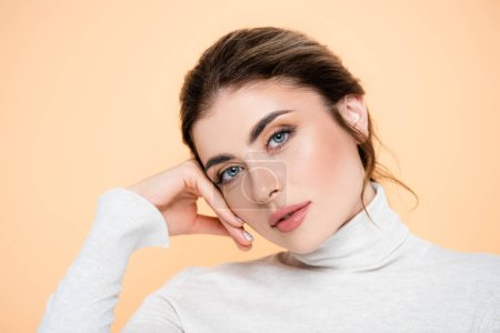Photo for Stylish woman in turtleneck looking at camera while touching face isolated on peach - Royalty Free Image