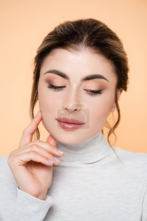 sensual woman in turtleneck touching face isolated on peach