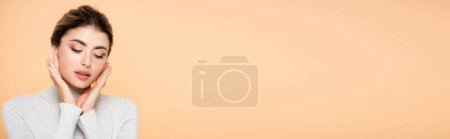 Photo for Horizontal image of woman in turtleneck touching face with closed eyes isolated on peach - Royalty Free Image