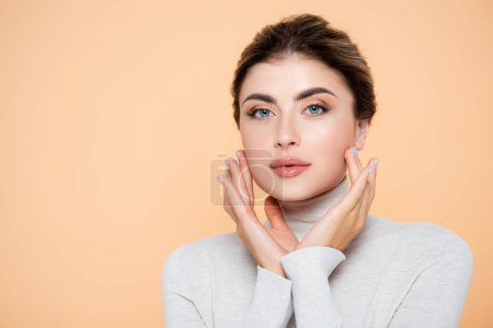 Photo for Sensual woman in turtleneck touching face while looking at camera isolated on peach - Royalty Free Image