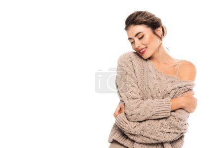joyful woman in openwork sweater hugging herself with closed eyes isolated on white
