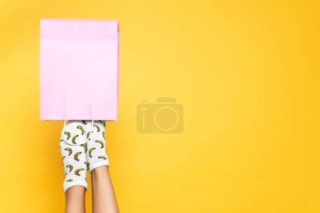 Draufsicht der Frau mit Socken, die Füße in rosa Papiertüte stecken, isoliert auf gelbem Hintergrund