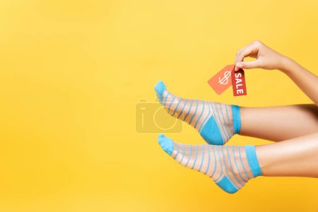 Photo pour Cropped view of woman wearing striped socks, holding tags with dollar symbol and sale word isolated on yellow - image libre de droit