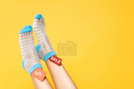 Photo for Cropped view of female legs in socks with blue stripes and tags with dollar symbol and sale word isolated on yellow - Royalty Free Image
