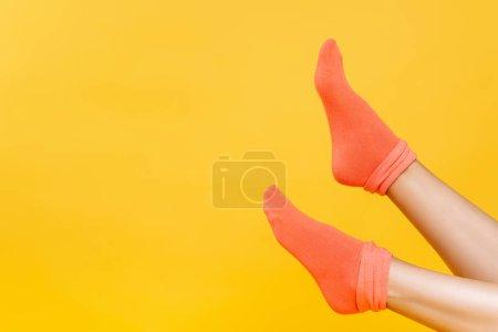 Photo pour Vue recadrée des jambes féminines en chaussettes orange douce isolées sur jaune - image libre de droit