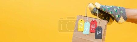 Photo pour Sac en papier avec étiquettes de vente suspendues sur les jambes de la femme dans des chaussettes isolées sur jaune, bannière - image libre de droit