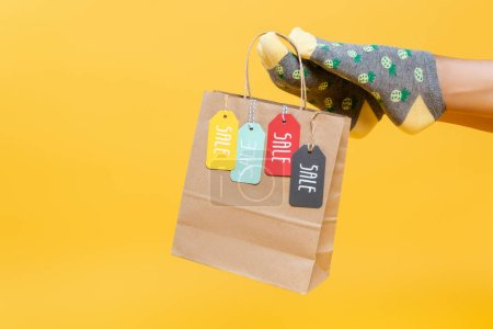 Photo for Cropped view of paper bag with sale tags hanging on woman leg in socks isolated on yellow - Royalty Free Image