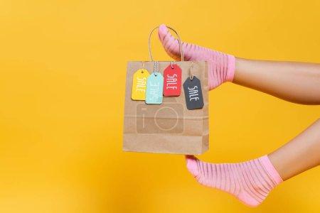 Photo pour Vue recadrée du sac en papier avec des étiquettes de vente suspendues sur les jambes de la femme dans des chaussettes isolées sur jaune - image libre de droit